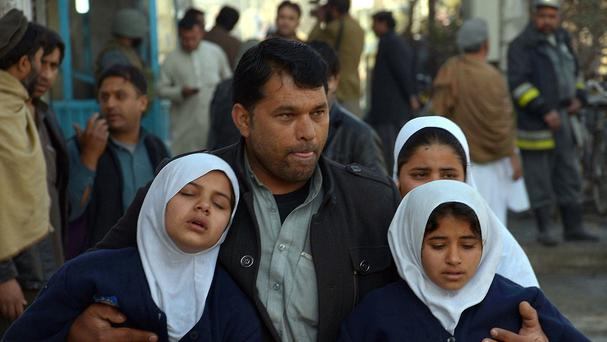 A man carries two schoolgirls away from the site in Jalalabad. (AP)