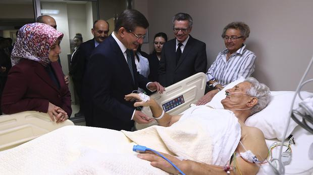 Turkey's Prime Minister Ahmet Davutoglu visits a victim of Tuesday's explosion in Istanbul. (AP)