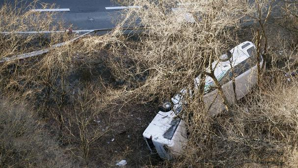The ski tour bus lies on its side after veering off the mountainside road (Kyodo News/AP)