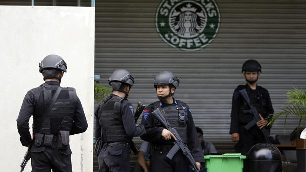 Indonesian police officers on guard near the Starbucks cafe where the attack took place (AP)