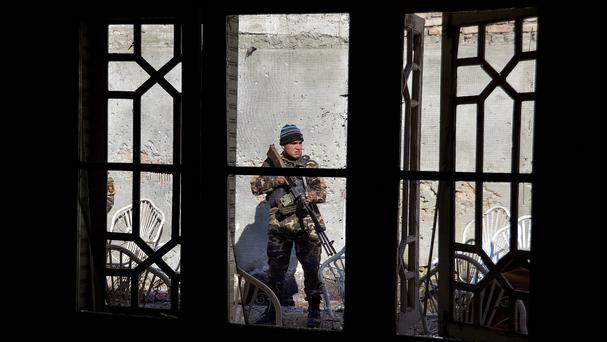 A member of the Afghan security forces stands guard at the site of a suicide attack which took place inside a residential house in Jalalabad (AP)