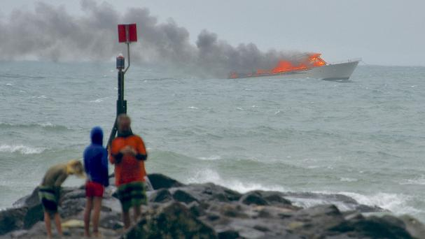 People stand on the shoreline as a tourist boat carrying 60 people burns out at sea off the coast of Whakatane, New Zealand (Whakatane Beacon via AP)