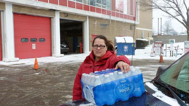 A resident of Flint picks up a case of bottled water outside a fire station (AP)
