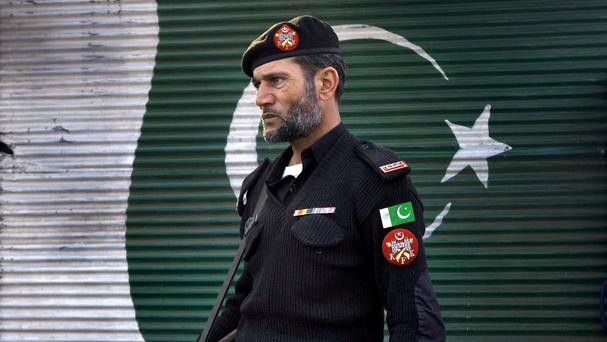 A police officer stands guard close to the site of a suicide attack in Peshawar, Pakistan (AP)