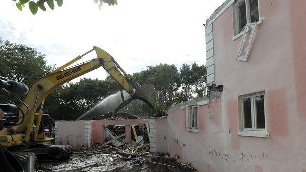 A bulldozer demolishes the waterfront mansion formerly owned by Colombian drug lord Pablo Escobar (AP)