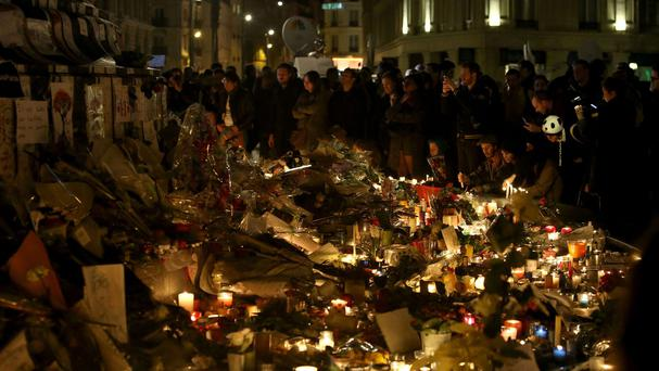 Crowds look at floral tributes and candles left at Place de la Republique in Paris, following the terrorist attacks in the city