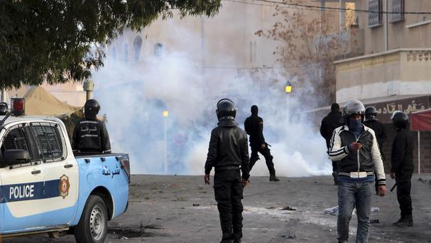 Police forces stand by tear gas during clashes in the city of Ennour, near Kasserine, Tunisia (AP)