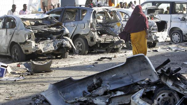 Somalis walk past the wreckage of vehicles outside a beachfront restaurant following an overnight siege in Mogadishu (AP)
