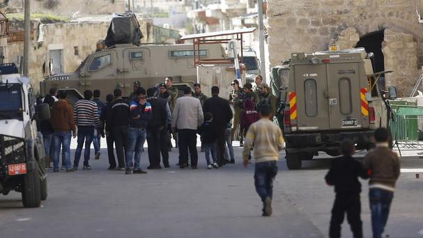 Israeli security forces stand guard as Jewish settlers are forced out of two homes in Hebron (AP)