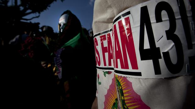 Relatives of 43 missing students at a Boxing Day protest in Mexico City - three more suspects have been arrested (AP)
