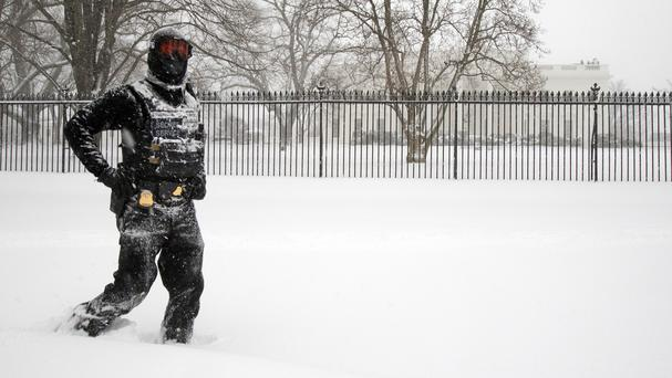 A uniformed US Secret Service police officer walks on a snow-covered walkway outside the White House in Washington (AP)