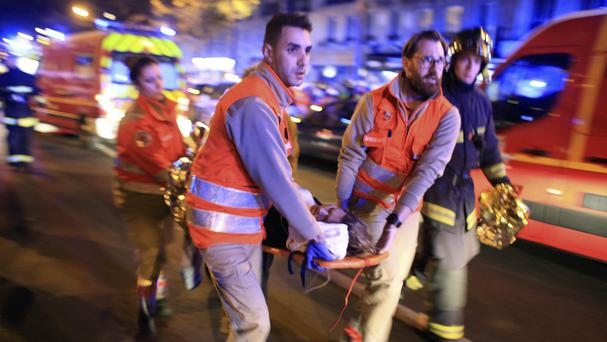 A woman is evacuated from the Bataclan concert hall after gunmen attacked the venue in the Paris terror attacks (AP)