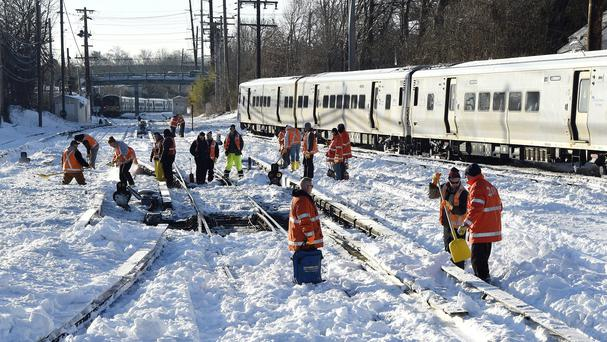 Workers clear the tracks of snow at the Port Washington branch of the Long Island Railroad in Port Washington, New York (AP)