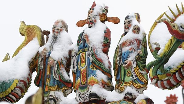 Snow sits on the Chinese god statues at the Pinglin temple in the high mountain area of New Taipei City, Taiwan (AP)