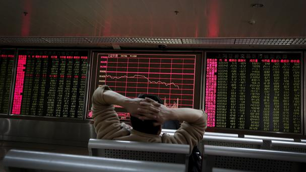 A man looks at an electronic board displaying stock prices at a brokerage house in Beijing (AP)