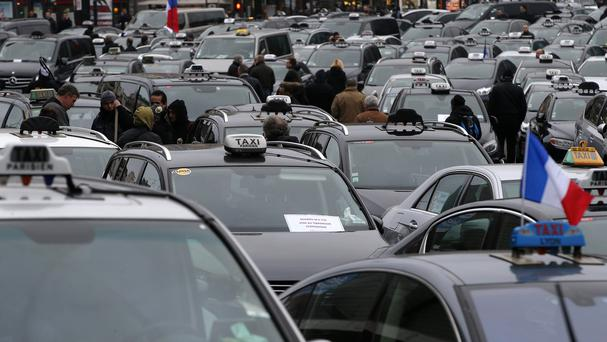 Taxi drivers on strike stand next to their cars as they demonstrate in Paris (AP)