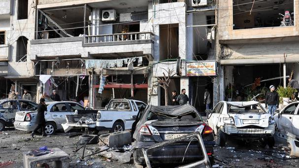 Syrian citizens gather at the scene where twin bombs exploded at a government-run security checkpoint in Homs province, Syria (SANA via AP)