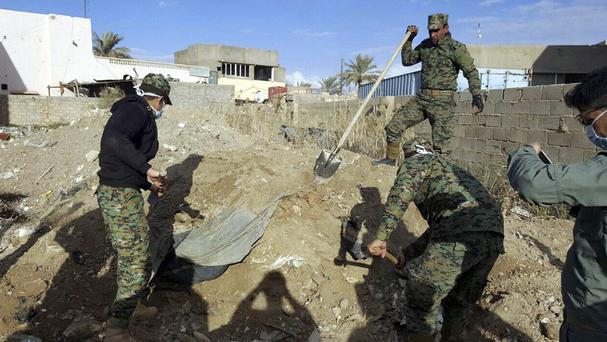 Iraqi security forces work at the site of a mass grave believed to contain the bodies of Iraqi civilians killed by IS militants in Ramadi (AP)