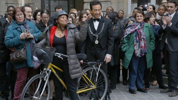 Christiane Taubira waves prior to leaving the French justice ministry on a bike in Paris (AP)