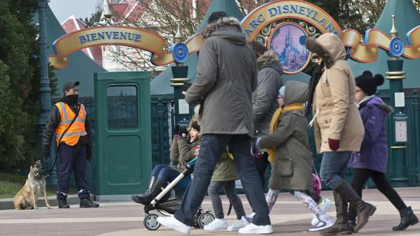 A private security guard patrols with his dog outside Disneyland Paris in Marne-la-Vallee, east of Paris (AP)