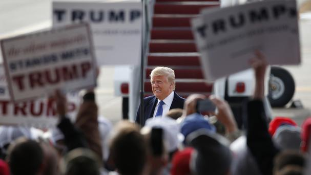 Republican front-runner Donald Trump surrounded by supporters at Dubuque Regional Airport, Iowa (AP)