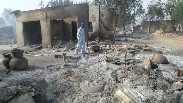 A man walks past burnt-out houses following an attack by Boko Haram in Dalori village, Nigeria (AP)