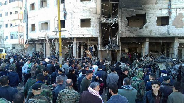 Syrians gather where three bombs exploded in Sayyda Zeinab, a predominantly Shiite Muslim suburb of the Syrian capital (SANA via AP)