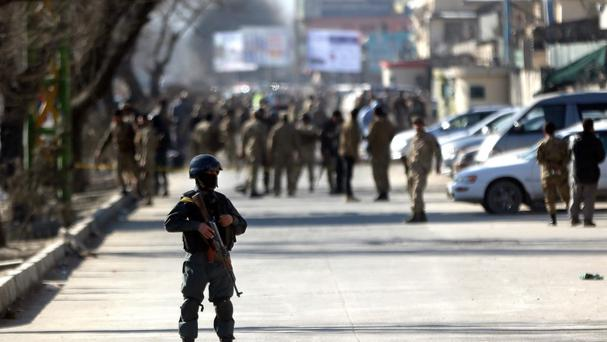 Afghan security forces inspect the site of a suicide attack at the gate of a police compound in Kabul, Afghanistan. (AP)