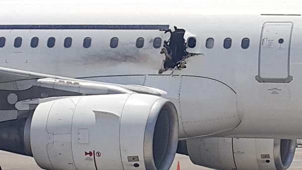 A gaping hole in the plane forced it to make an emergency landing at Mogadishu's international airport. (AP)
