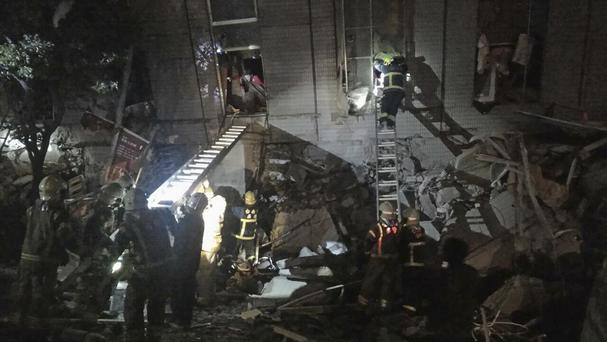 Rescuers are seen entering an office building that collapsed on its side (AP)