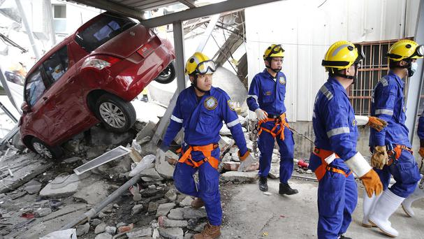 Rescue workers search a collapsed building from an early morning earthquake in Tainan (AP)