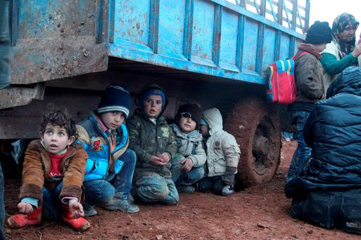 SHELTER FROM THE STORM OF WAR: A girl and her brothers, who fled the violence from the Isil-controlled area of al-Bab around Aleppo with their families, wait as they are stuck in the small Syrian village of Akda to cross into Turkey last week. Turkey's border guards prevented the displaced people from approaching their border, activists said. Photo: Abdalrhman Ismail/Reuters
