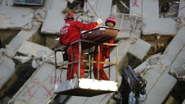 Two emergency workers carry a victim recovered from a collapsed building in Tainan (AP)