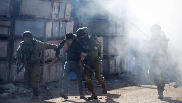 Israeli soldiers arrest a Palestinian protester during clashes in the West Bank (AP)