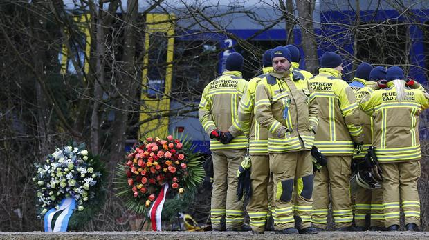 Rescue workers stand beside wreaths in front of two trains that collided head-on near Bad Aibling, Germany (AP)