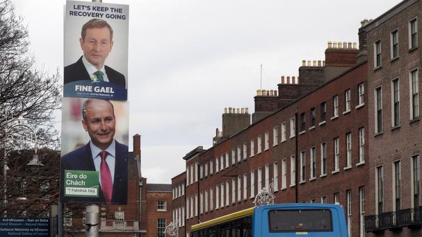 Election posters of prime minister Enda Kenny, top, and Fianna Fail leader Micheal Martin compete for space in Merrion Square, Dublin (AP)