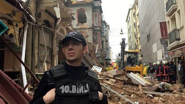 A police officer stands guard as firefighters investigate after the collapse in Istanbul (AP)