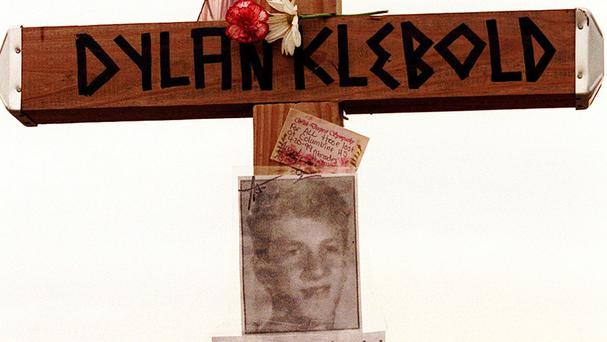 A cross bearing the name and likeness of Dylan Klebold and a message saying 'How can anyone forgive you?' on a hill in Littleton, Colorado, near Columbine High School (Denver Rocky Mountain News /AP)