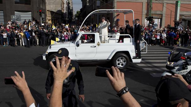 Pope Francis waves to people lining the route as he heads for the Basilica of the Virgin of Guadalupe in Mexico City (AP)