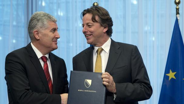 Bosnia president Dragan Covic (left) and Dutch foreign minister Bert Koenders participate in a handover ceremony of the EU membership application (AP)