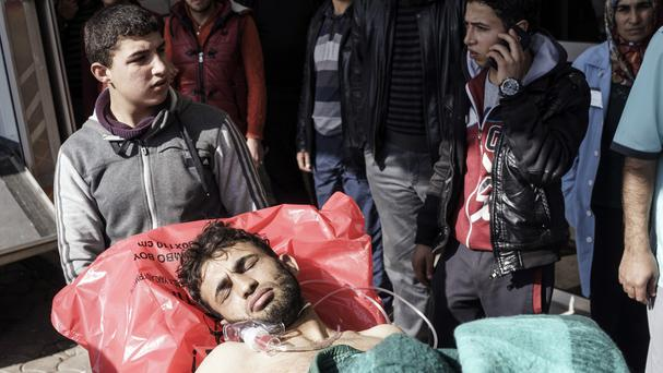 A wounded Syrian man is carried to a hospital in Kilis, Turkey, after an airstrike in the northern Syrian province of Idlib destroyed a makeshift clinic (AP)