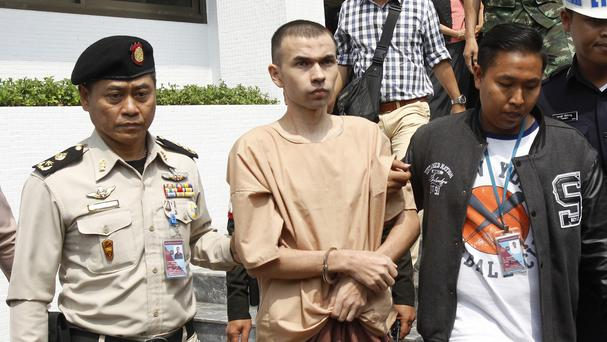 Thai officers escort Bilal Mohammad, centre, from a military court in Bangkok (AP)