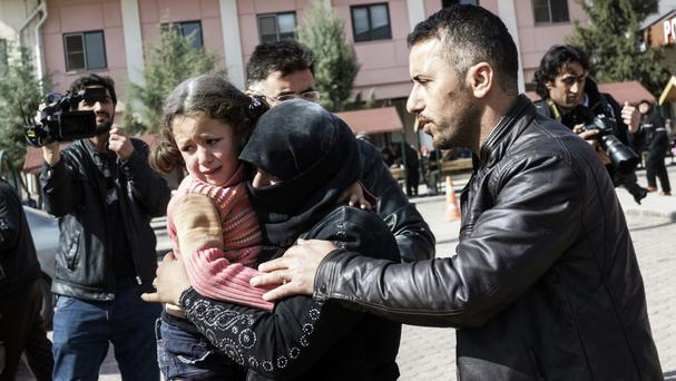 A Turkish man helps a Syrian woman carrying a wounded girl to a hospital in Kilis after a hospital in Syria was bombed (AP)