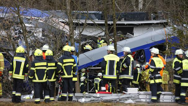 Rescue personnel stand in front of two trains that collided head-on near Bad Aibling in southern Germany (AP)