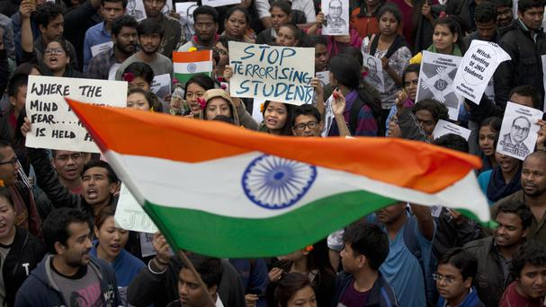 Students wave an Indian flag and shout slogans during a protest at the Jawaharlal Nehru University (AP)