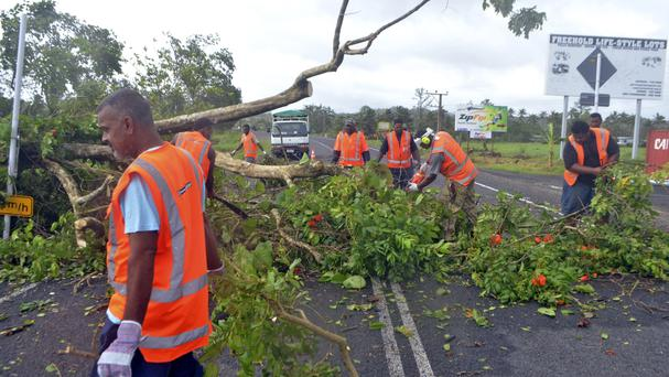 Road workers remove a fallen tree blocking a road near Lami, Fiji, after cyclone Winston ripped through the country (AP)