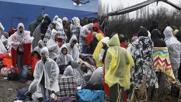 Refugees from Afghanistan wait for a permission to cross the border from Macedonia at a checkpoint near the Tabanovce transit centre (AP)