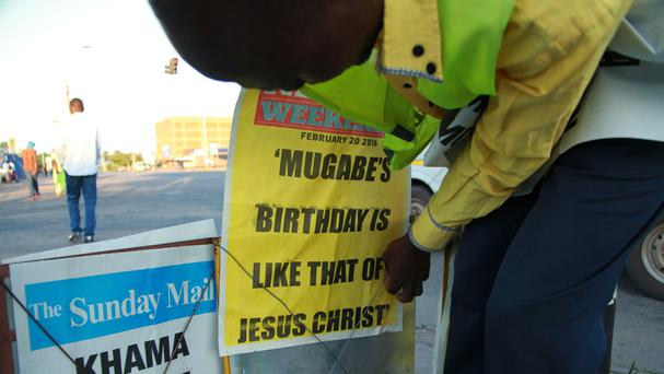 A newspaper vendor in Harare places a banner relating to Robert Mugabe's birthday (AP)