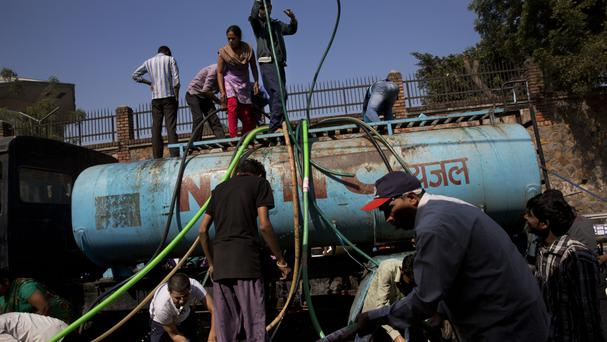 Residents crowd around a tanker delivering drinking water at a slum in New Delhi (AP)