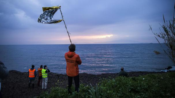 A volunteer waves a makeshift flag to guide a dinghy with refugees and migrants as they approach from the Turkish coast to Mytilene, Lesbos, Greece (AP)